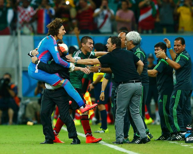 Mexico's coach Miguel Herrera (2nd L) celebrates with goalkeeper Guillermo Ochoa the second goal of their team during their 2014 World Cup Group A soccer match against Croatia at the Pernambuco arena in Recife June 23, 2014. (REUTERS/Eddie Keogh)