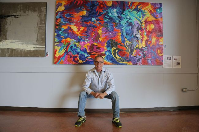 Steve Tracy sits beneath his painting, Big Bang Primarily, part of Corporate Colours, an exhibition on at Art With Panache. (Richard Gilmore/Special to QMI Agency)
