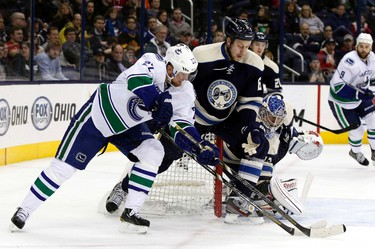 Vancouver Canucks' Daniel Sedin (22) fights for the puck in front of the goal with Columbus Blue Jackets' Nikita Nikitin (6) and Sergei Bobrovsky (C) during the first period of their NHL hockey game in Columbus, Ohio March 7, 2013.  REUTERS/Matt Sullivan  (UNITED STATES - Tags: SPORT HOCKEY)