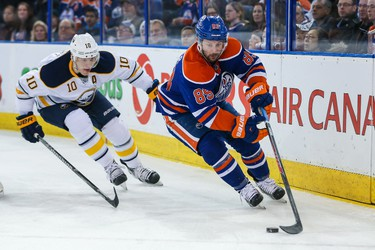 Mar 20, 2014; Edmonton, Alberta, CAN; Edmonton Oilers center Sam Gagner (89) and Buffalo Sabres defenseman Christian Ehrhoff (10) battle for the puck during the first period at Rexall Place. Mandatory Credit: Sergei Belski-USA TODAY Sports
