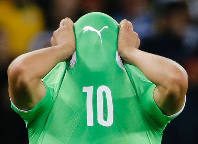 Algeria's Sofiane Feghouli covers his face with his jersey as he reacts to his team's loss at the end of their World Cup game against Germany at the Beira Rio stadium in Porto Alegre, Brazil on Monday, June 30, 2014. (Edgard Garrido/Reuters)