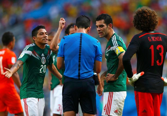 Mexico's players discuss with referee Pedro Proenca of Portugal after he called a penalty in favour of the Netherlands during their 2014 World Cup round of 16 game at the Castelao arena in Fortaleza June 29, 2014. (REUTERS/Eddie Keogh)