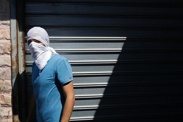 A Palestinian stone-thrower stands during clashes with Israeli police in Shuafat, an Arab suburb of Jerusalem July 2, 2014.   REUTERS/Baz Ratner