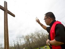 Father Darius Bilran sprinkles holy water on a wooden cross prominently featured in the church cemetery of St. Anthony Church located at Zbaraz. (Brook Jones/Selkirk Journal/QMI Agency)