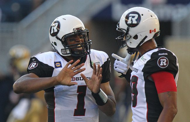 RedBlacks quarterback Henry Burris speaks with Marcus Henry following a touchdown during CFL action against the Blue Bombers in Winnipeg on Thursday, July 3, 2014. (Kevin King/QMI Agency)