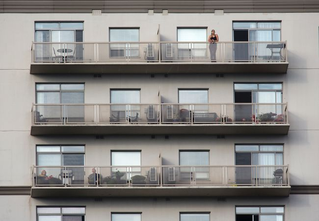 A downtown resident looks out over the city from her balcony in London. DEREK RUTTAN/ The London Free Press /QMI AGENCY