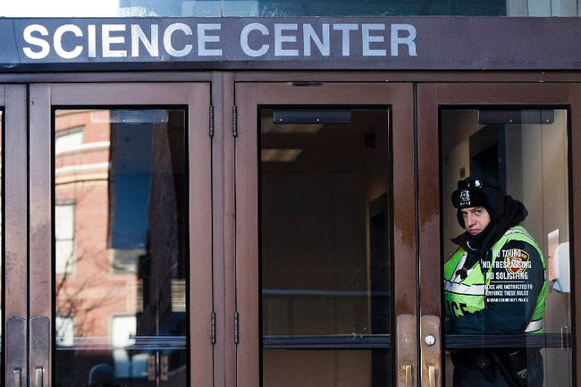 A police officer looks out of an entrance to the Science Center at Harvard University in Cambridge, Mass., in this Dec. 16, 2013 file photo. REUTERS/Dominick Reuter