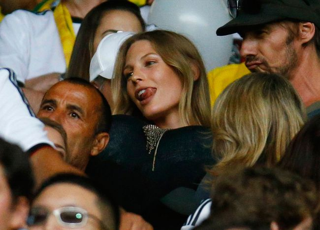 A photo shows Sarah Brandner, the girlfriend of Germany's Bastian Schweinsteiger, holding balloons before putting them under her shirt while waiting for the start of the 2014 World Cup semi-finals between Brazil and Germany at the Mineirao stadium in Belo Horizonte July 8, 2014. (REUTERS/Kai Pfaffenbach)