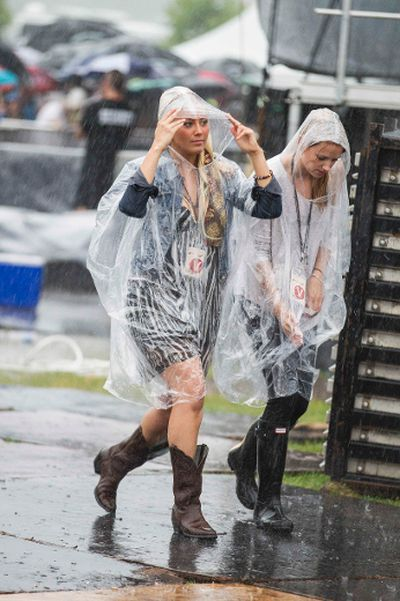 Two woman endure a torrential downpour while awaiting Styx hitting the stage at Bluesfest in Ottawa on Tuesday July 8, 2014. Errol McGihon/Ottawa Sun/QMI Agency