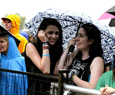 Concert goers take shelter from the rain before Styx hit the stage at Bluesfest in Ottawa. July 8, 2014. Errol McGihon/Ottawa Sun/QMI Agency