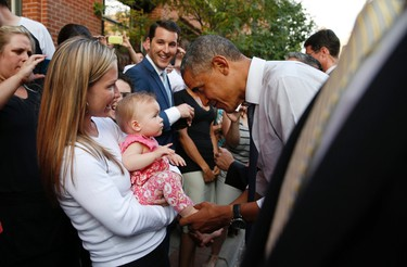 U.S. President Barack Obama greets a baby during a walkabout in Denver July 8, 2014. Obama will speak about the economy at an event in Denver tomorrow.   REUTERS/Kevin Lamarque