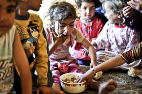 Syrian children eat lunch in a disused house on June 28, 2014 in the Fikirtepe area of Istanbul. Hundreds of Syrian refugees live in empty houses in an area of 32 hectares undergoing an urban transformation project in Fikirtepe, which is on standby due to ongoing negotiations between the owners of the houses and the company running the project.  AFP PHOTO / OZAN KOSE