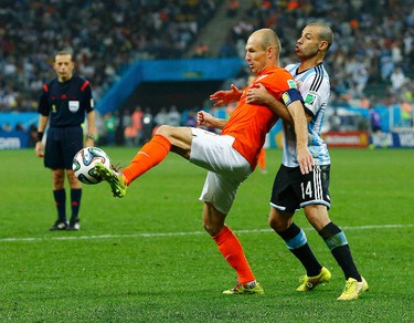 Arjen Robben (L) of the Netherlands fights for the ball with Argentina's Javier Mascherano during their 2014 World Cup semi-finals at the Corinthians arena in Sao Paulo July 9, 2014.