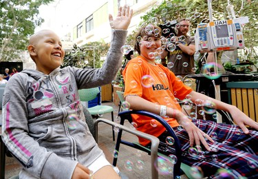 Kayleigh Morin, 9, and Karsten Huth, 15, play in bubbles during the Edmonton International Street Performers Festival Comedy Cares performance at the Stollery Children�s Hospital in Edmonton Alta., on Wednesday July 9, 2014. David Bloom/Edmonton Sun/QMI Agency