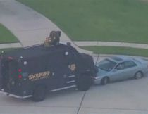 A still image taken from KPRC-TV aerial video footage shows a Harris County Sheriff's Office High Risk Operations Unit vehicle and a suspect's vehicle in a standoff at a residential neighborhood following a shooting incident in Spring, Texas July 9, 2014.   REUTERS/KPRC-TV