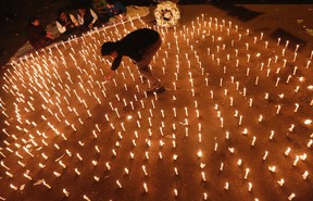 A protester lights candles during a candlelight vigil to mark the first anniversary of the Delhi gang rape, in New Delhi in this December 16, 2013 file photo. (REUTERS/Adnan Abidi)