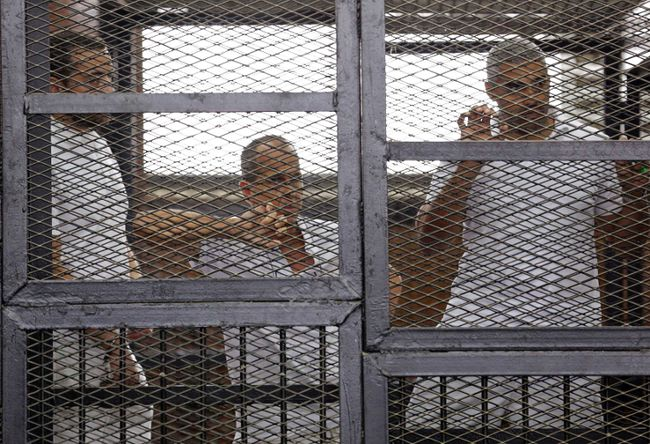 Al Jazeera journalists (L-R)  Baher Mohamed, Peter Greste and Mohammed Fahmy stand behind bars in a court in Cairo.