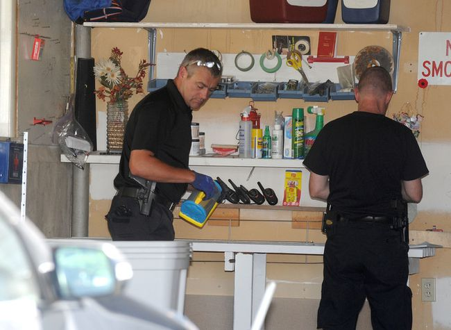 Calgary city police sift through articles in the garage on Saturday July 12, 2014 of the home where five-year-old Nathan O'Brien and his grandparents Alvin and Kathryn Liknes went missing in Parkhill in SW Calgary, Alta. Stuart Dryden/Calgary Sun/QMI Agency