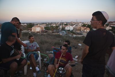 Israelis smoke water pipe at a lookout hill near Sderot, opposite the northern Gaza Strip July 13, 2014. Thousands fled their homes in a Gaza town on Sunday after Israel warned them to leave ahead of threatened attacks on rocket-launching sites, on the sixth day of an offensive that Palestinian officials said has killed at least 160 people. Militants in the Hamas-ruled Gaza Strip kept up rockets salvoes deep into the Jewish state and the worst bout of Israel-Palestinian bloodshed in two years showed no signs of abating, and Western foreign ministers meeting on Sunday said a ceasefire was an urgent priority. REUTERS/Nir Elias