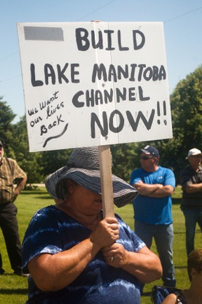A Lake Manitoba resident holds up a sign demanding an emergency outlet be built on Lake Manitoba immediately. About 80 farmers and residents came to protest at Mark Peters' farm, which is at the farthest end of the Portage Diversion, on Tuesday regarding the province's announcement it will take seven years to build an emergency oulet for the lake. (Svjetlana Mlinarevic/The Graphic/QMI Agency)