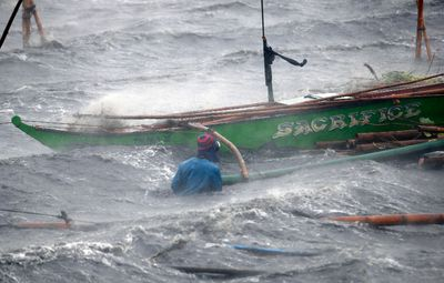A fisherman secures his boat as Typhoon Rammasun (locally named Glenda) hits the coastal town of Imus, Cavite southwest of Manila, July 16, 2014.    REUTERS/Erik De Castro