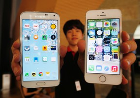 A sales assistant holding Samsung Electronics' Galaxy S5 smartphone (L) and Apple Inc's iPhone 5 smartphone (R) poses for photographs at a store in Seoul July 16, 2014. REUTERS/Kim Hong-Ji