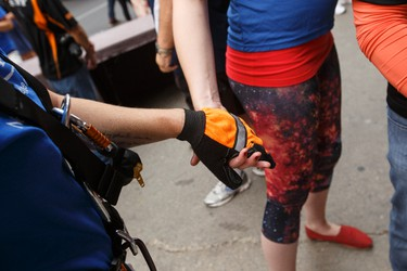 Shelby Asmundson (right), a wish recipient, holds communications coordinator Katie Willis hand after completing her 20-storey descent during Make-A-Wish Northern Alberta's Rope for Hope fundraiser at the Westin hotel in Edmonton, Alta., on Wednesday, July 16, 2014. The fundraiser helps raise awareness to allow the organization to grant wishes to sick children. Ian Kucerak/Edmonton Sun/QMI Agency