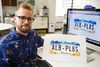 <p>Derek Anton, creative director at Graphos, an Edmonton-based design firm, poses with the Alberta licence plate template that he came up with last week at the Graphos office in Edmonton, Alta., on Wednesday, July 16, 2014. Codie McLachlan/Edmonton Sun/QMI Agency