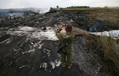An armed pro-Russian separatist takes pictures at the site of a Malaysia Airlines Boeing 777 plane crash near the settlement of Grabovo in the Donetsk region, July 17, 2014. The Malaysian airliner Flight MH-17 was brought down over eastern Ukraine on Thursday, killing all 295 people aboard and sharply raising the stakes in a conflict between Kiev and pro-Moscow rebels in which Russia and the West back opposing sides.    REUTERS/Maxim Zmeyev