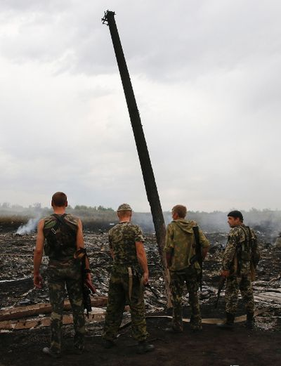 Armed pro-Russian separatists stnad at the site of a Malaysia Airlines Boeing 777 plane crash near the settlement of Grabovo in the Donetsk region, July 17, 2014. The Malaysian airliner Flight MH-17 was brought down over eastern Ukraine on Thursday, killing all 295 people aboard and sharply raising the stakes in a conflict between Kiev and pro-Moscow rebels in which Russia and the West back opposing sides.  REUTERS/Maxim Zmeyev