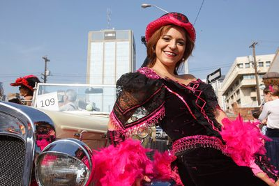 Klondike Kate, a.k.a Maria Harrigan, poses for a photo with a classic 1930 Ford Model A car before the K-Days Parade in downtown Edmonton, Alta., on Friday, July 18, 2014. The fair runs at Northlands until July 27. Ian Kucerak/Edmonton Sun/QMI Agency