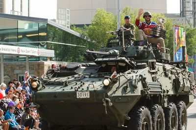 A member of the Princess Patricia's Canadian Light Infantry and Edmonton Oil Kings forward Mitch Moroz wave during the K-Days Parade in downtown Edmonton, Alta., on Friday, July 18, 2014. The fair runs at Northlands until July 27. Ian Kucerak/Edmonton Sun/QMI Agency