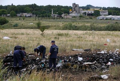 Members of the Ukrainian Emergencies Ministry work at a crash site of Malaysia Airlines Flight MH17, near the village of Hrabove, Donetsk region July 20, 2014. Ukraine accused Russia and pro-Moscow rebels on Saturday of destroying evidence to cover up their guilt in the shooting down of a Malaysian airliner that has intensified a showdown between the Kremlin and Western powers. REUTERS/Maxim Zmeyev (UKRAINE - Tags: DISASTER POLITICS TRANSPORT)