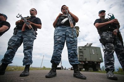 Armed pro-Russian separatists stand guard at a crash site of Malaysia Airlines Flight MH17, near the village of Hrabove, Donetsk region July 20, 2014.REUTERS/Maxim Zmeyev