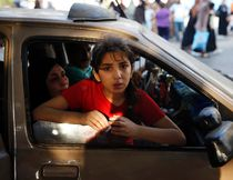 A Palestinian girl looks out from a vehicle while fleeing the Shujayeh neighbourhood during heavy Israeli shelling in Gaza City July 20, 2014. Israel said on Sunday it had expanded its ground offensive in Gaza and militants kept up rocket fire into the Jewish state with no sign of a diplomatic breakthrough to end the worst fighting between Israel and Hamas in two years. Gaza residents said land and naval shellings were the heaviest in 13 days of fighting. Explosions rocked the coastal enclave overnight and shells fired by Israeli naval forces lit up the sky. REUTERS/Finbarr O'Reilly