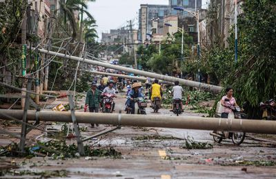 Residents travel on a street blocked by fallen electricity poles after Typhoon Rammasun hit Leizhou, Guangdong province July 19, 2014. (REUTERS/Stringer)
