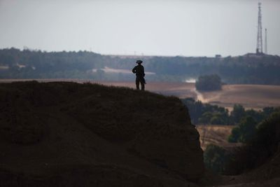 An Israeli soldier stands guard on a hill outside central Gaza Strip July 19, 2014.   REUTERS/Amir Cohen