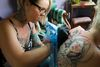 Aimee Allen fills in the tattoo of St. Michael on the back of Candace Amoun at Taste of Ink on Wellington Street in London. (Mike Hensen/The London Free Press/QMI Agency)