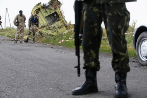 An armed pro-Russian separatist stands guard as monitors from the Organization for Security and Cooperation in Europe (OSCE) and members of a Malaysian air crash investigations team inspect the crash site of Malaysia Airlines Flight MH17 near the village of Hrabove (Grabovo), Donetsk region July 22, 2014. Almost 300 people were killed when the Malaysian airliner went down last Thursday. (REUTERS/Maxim Zmeyev)