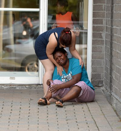 A woman collapses in tears on Thursday, July 24, 2014 after receiving news that five members of the Somda family likely died in the crash of an Air Algerie plane in Mali. The woman was in front of the Somda family's apartment building in Longueuil, Que., on Montreal's south shore. MAXIME DELAND / QMI AGENCY