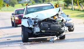 Cars swerve around an SUV with severe frontal damage on Hickory Drive after a collision with another SUV at the intersection of Egremont Drive July 25 at approximately 8:30 a.m. ELENA MAYSTRUK/ AGE DISPATCH/ QMI AGENCY