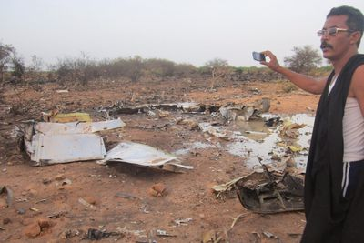 A man takes a picture of the crash site of the Air Algerie flight AH5017 near the northern Mali town of Gossi, July 24, 2014. (REUTERS/Stringer)