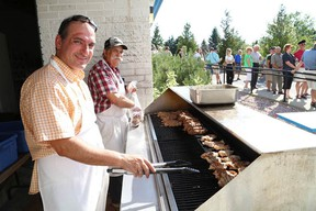 JOHN LAPPA/THE SUDBURY STAR/QMI AGENCY Paul Vlahos, left, and George Alexakis prepare food  for a large crowd for dinner at the annual Greek Festival of Sudbury at St. Nicholas Greek Orthodox Church on Ester Road in Sudbury, ON. on Friday, July, 25, 2014. The festival includes music, dance performances, a refreshment tent and activities for children. The festival runs until Sunday.