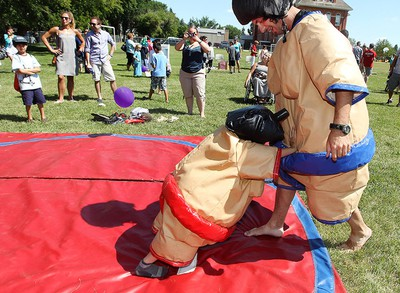 Chase Fletcher, 6, pushes his father Jason Willacy out of the ring as they sumo wrestle during the 2nd annual Ronald McDonald House Northern Alberta Block Party, near 7726 - 107 St., in Edmonton Alta., on Sunday July 27, 2014. David Bloom/Edmonton Sun/ QMI Agency