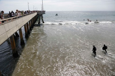 Rescue divers enter the waters near a pier for victims of a lightning strike that injured people in Venice, California July 27, 2014. REUTERS/Jonathan Alcorn