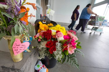 Shoppers push a cart past flowers and stuffed toys left in memorial to Addison Hall, the six-year-old girl who was killed Friday after a car reversed through the front doors of the Costco store on Wellington Road, in London, Ontario on Sunday July 27, 2014.  A Monte Carlo driven by a woman in her sixties suddenly backed into the entrance of the big-box store, reversing between two pillars before smashing through the glass doors and striking Danah McKinnon Bozek and her daughters Miah, 3, and Addison.  McKinnon Bozek's condition was upgraded to fair over the weekend, say police, however Miah and McKinnon Bozek's baby, who was delivered by emergency caesarian-section on Friday, remain in critical condition.  Police are investigating what caused the car to crash into the store and whether any charges will be laid against the driver. CRAIG GLOVER/The London Free Press/QMI Agency