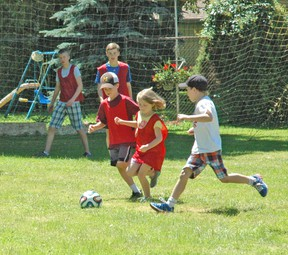 Assistant coaches Danny Kenyon (back left), and Cai Aldridge watch closely as Rhett Terpstra (left) and Ava Van Oostveen chase the ball in a game of soccer during the Upper Thames Missionary Church annual sports camp July 14-18. The camp included soccer, baseball and basketball and involved 50 participants. KRISTINE JEAN/MITCHELL ADVOCATE