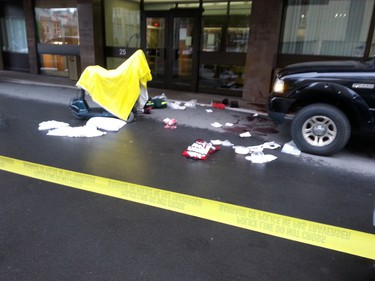 A pool of blood and medical supplies remain on the pavement beside a motor scooter outside the Embassy Suites on Cartier St. in downtown Ottawa Wednesday morning, where a man was stabbed overnight. (DOUG HEMPSTEAD Ottawa Sun)