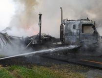 Members of the Belleville Fire Department (BFD) extinguish a fire in the eastbound lane on Hwy. 401, east of Hwy. 37, near Shannonville, Ont., after a tractor-trailer collided and burst into flames at approximately 6 a.m. on July 30, 2014. (Photo by Ray Ellis, Deputy Fire Chief at BFD)