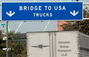A commercial automotive supplier truck passes under a sign leading to the Ambassador bridge crossing over to Detroit, Michigan from Windsor, Ontario September 28, 2013.  REUTERS/Rebecca Cook